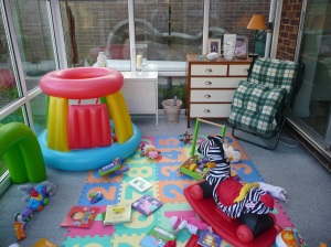 Conservatory before makeover strewn with toys