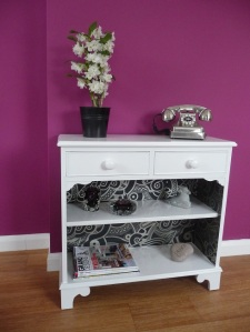 After makeover: white, fresh painted bookcase with dramatic wallpaper lining